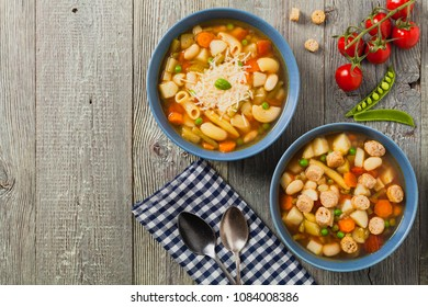Minestrone soup with pasta and cheese or crostini. Natural wooden background. Top view.