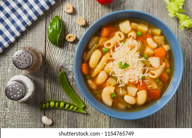 Minestrone soup with pasta and cheese. Natural wooden background. Top view.