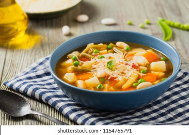 Minestrone soup with pasta and cheese. Natural wooden background. Front view.