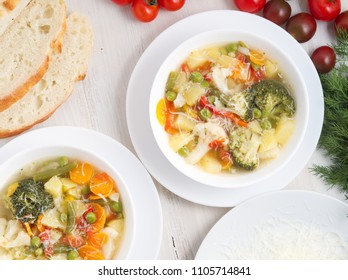 Minestrone soup. Vegetable soup with tomato, celery, carrot, zucchini, onion, pepper, broccoli. Top view, white table