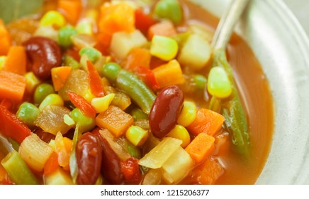 Minestrone-traditional Italian thick vegetable soup with seasonal vegetables-potatoes, carrots, onions, red and green beans, corn, peas, tomatoes with seasonings and spices with pasta or rice
