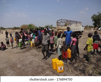 MINGKAMA, AWERIAL, LAKES STATE, SOUTH SUDAN - 2014 JANUARY 9 - Refugees and families are gathering near a water truck to collect drinking water
