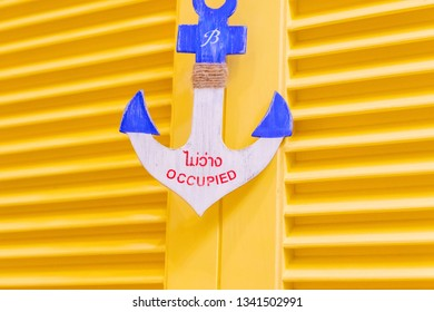 Mini anchor which is made to be an occupied sign on it with English and Thai alphabet and yellow wood background in Blueport Shopping mall Hua Hin, Thailand February 5, 2019