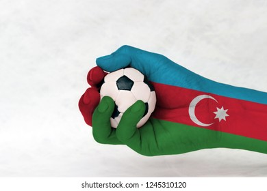 Mini ball of football in Azerbaijan flag painted hand on white background. Blue red and green with  crescent and star. Concept of sport or the game in handle or minor matter.
