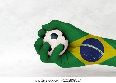 Mini ball of football in Brazil flag painted hand on white background. Concept of sport or the game in handle or minor matter. green yellow and blue color and world in center.