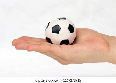 Mini ball of football in hand on white background. Concept of sport or the game in handle.