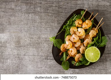 Mini barbecue with shrimps on a wooden skewer, grill, bbq. Simple background. Healthy food. Lifestyle