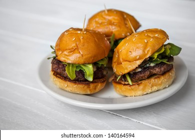 Mini Beef Sliders with Arugula on Sesame Seed Buns on a White Washed Wood Background