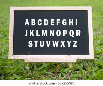 mini blackboard with alphabets a to z isolated on grass field background