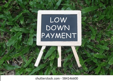 Mini Blackboard with word written 'LOW DOWN PAYMENT' on green grass background