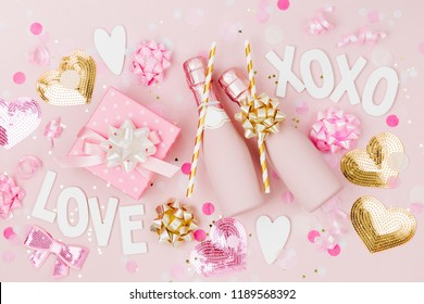 Mini bottles of champagne with confetti and tinsel on Pale Pink background.  Valentines day or birthday party concept theme. Flat lay, top view