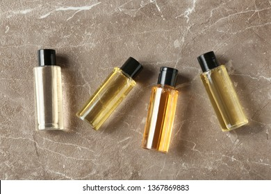 Mini bottles with cosmetic products on marble table, flat lay. Hotel amenities