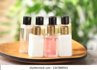 Mini bottles with cosmetic products on tray against blurred background, closeup. Hotel amenities