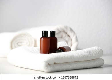Mini bottles with cosmetic products and towels on table against light background. Hotel amenities