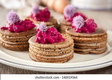 Mini buckwheat pancakes garnished with colorful beet salad and chives blossoms