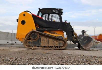 Mini bulldozer on a gravel road in a   construction site of a development urban area