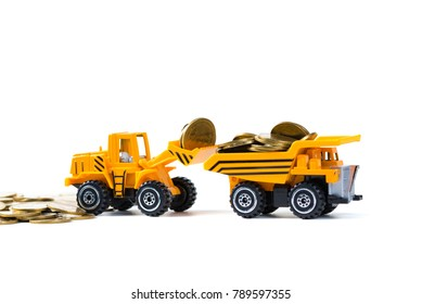 Mini bulldozer truck loading stack coin with pile of gold coin, isolated on white background with copy space, business finance and banking industrial concept idea.