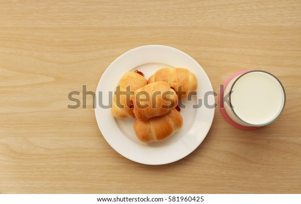 Mini bun bread in dish and milk on wooden table