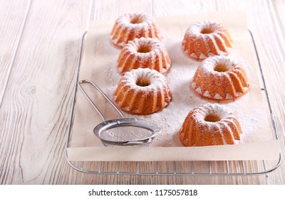 Mini bundt cakes with icing sugar on rack
