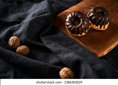 Mini cakes muffins with chokolate glaze on old rustic wooden board and walnuts on dark background, sweet concept