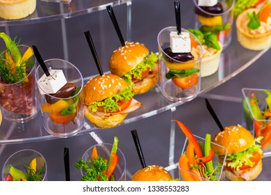 Mini canapes with cheese salads meat and seafood in plastic cups.