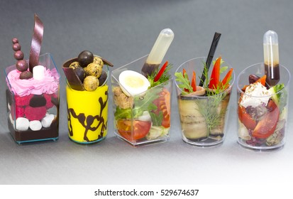 Mini canapes with desserts and meal salami vegetables in plastic cups on a gray background