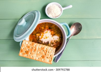Mini casserole of minestrone soup with cracker and parmesan cheese. Above view