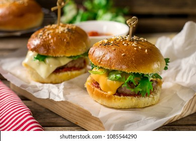 Mini cheeseburgers sliders with ground beef, cheddar, lettuce, onions and tomato sauce