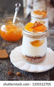 Mini cheesecake with apricots in two cups on wooden background