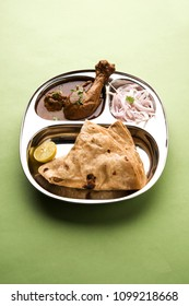 Mini chicken curry Thali with chapati/roti, popular indian lunch/dinner menu. served in a stainless steel oval plate with salad. selective focus