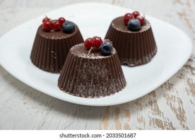 Mini-Schokoladenkuchen mit frischen Heidelbeeren und rotem Johannisbeeren