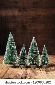 mini christmas tree wood on rustic wooden table and dark brown hardwood wall.winter holiday seasonal greeting card.leave space to adding text or design