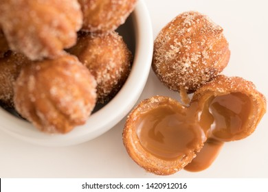 Mini Churros filled with dulce de leche (milk caramel)  on white background. Selective focus.