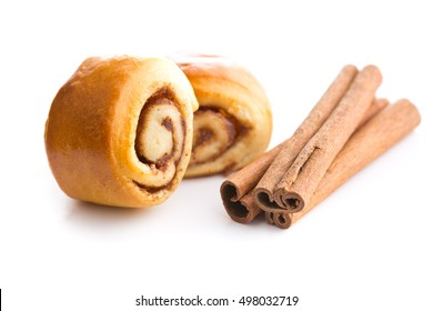 Mini cinnamon buns and cinnamon sticks isolated on white background.