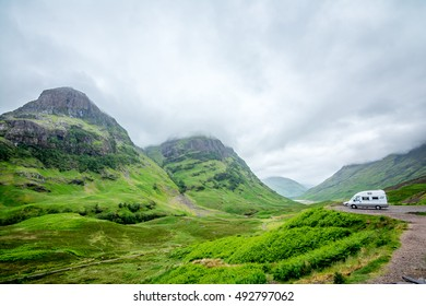 Mini coach parking by Glen Coe (Gaelic: Gleann Comhann) - a spectacular glen of volcanic origins, in the Highlands of Scotland, lying in the north of Argyll, close to the border with Lochaber.