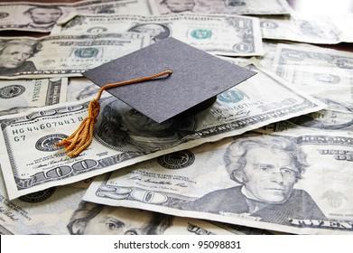 mini college graduation cap on cash