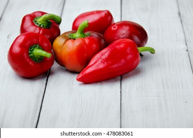 mini colored sweet peppers on a wooden background