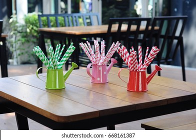 Mini colourful watering pot and straw paper on the table