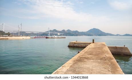 A mini concrete pier in Innoshima Island with a long suspension bridge in the background called 'Innoshima Bridge' which connects Mukoujima Island and Innoshima Island in the Shikoku Region of Japan.