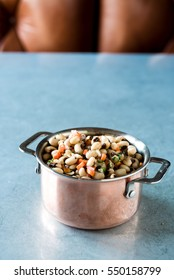 Mini copper pot of Southern black eyed pea salad with fresh herbs, carrots and red onion tossed in oil on metal surface with brown leather seat in the background.