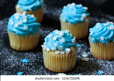 Mini Cupcakes with blue frosting and snowflakes sprinkles, selective focus