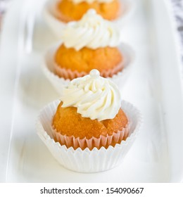 mini cupcakes decorated with white frosting and little pearls. Selective focus