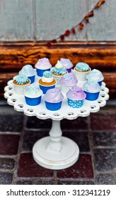Mini cupcakes on a wooden white stand. Dessert in autumn decoration with dry yellow leaves. Natural light