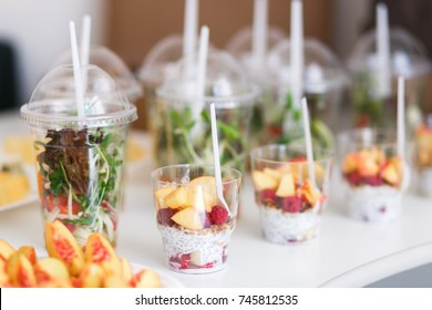 Mini desserts and healthy vegetable microgreen salads in plastic cups canaps. Catering served table