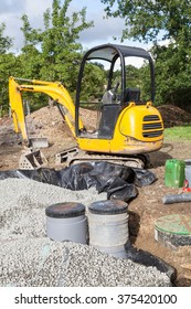 A mini digger or excavator being used to install a   gravel filter bed and pump for a domestic septic tank to purify the wastewater and sewage in a new installation
