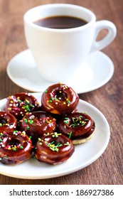 Mini donuts coated with chocolate and sprinkles with cup of coffee