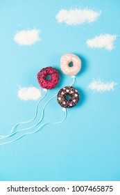 Mini donuts on blue background, creative food minimalism, donut in a shape of balloon in the sky with clouds made of coconut, top view