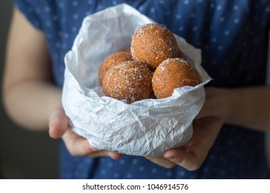 mini donuts in a paper bag in the hands of a girl
