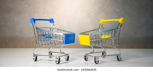 Mini empty blue and yellow shopping cart or shopping trolley on the table. Supermarket grocery push cart. Buying concept.