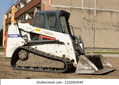 A Mini excavator bobcat standing at construction site